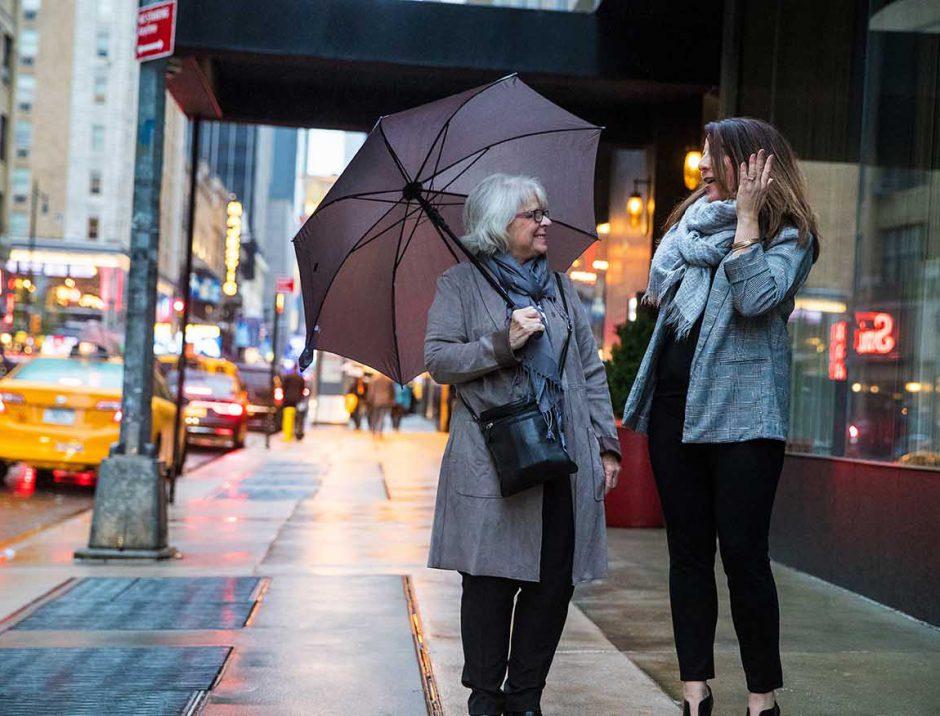 two women walking through new york city on rainy day