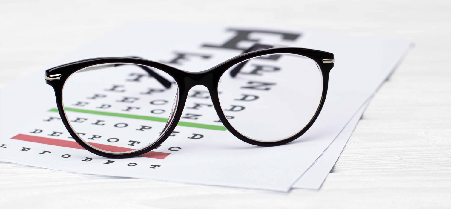 photo of glasses on top of eye exam chart