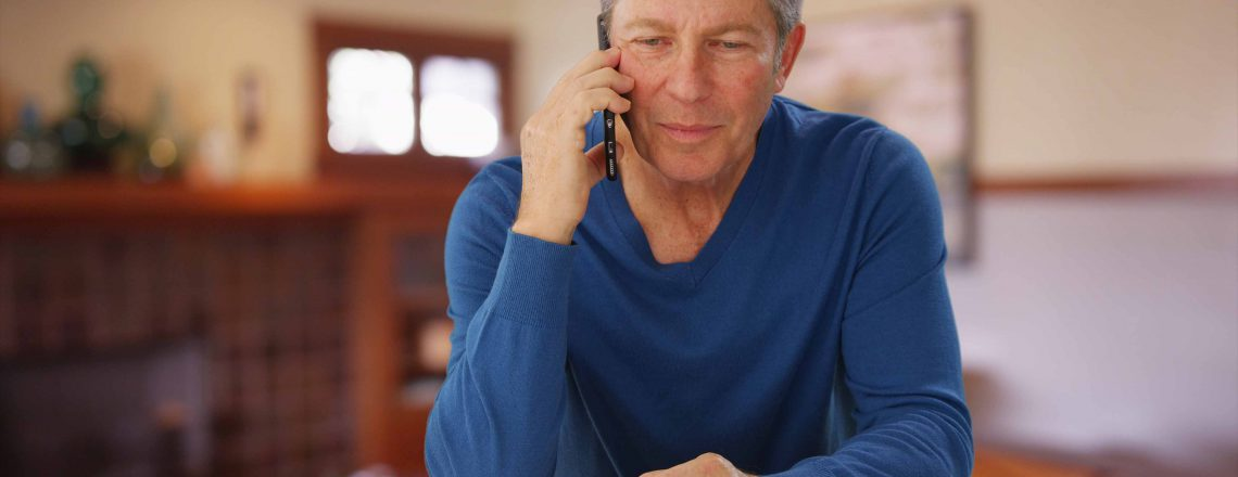 Older man on phone in home