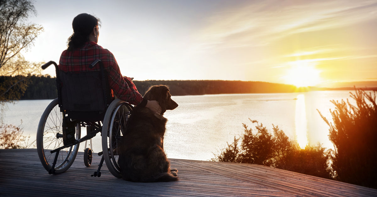 Woman in wheelchair with her dog at sunset