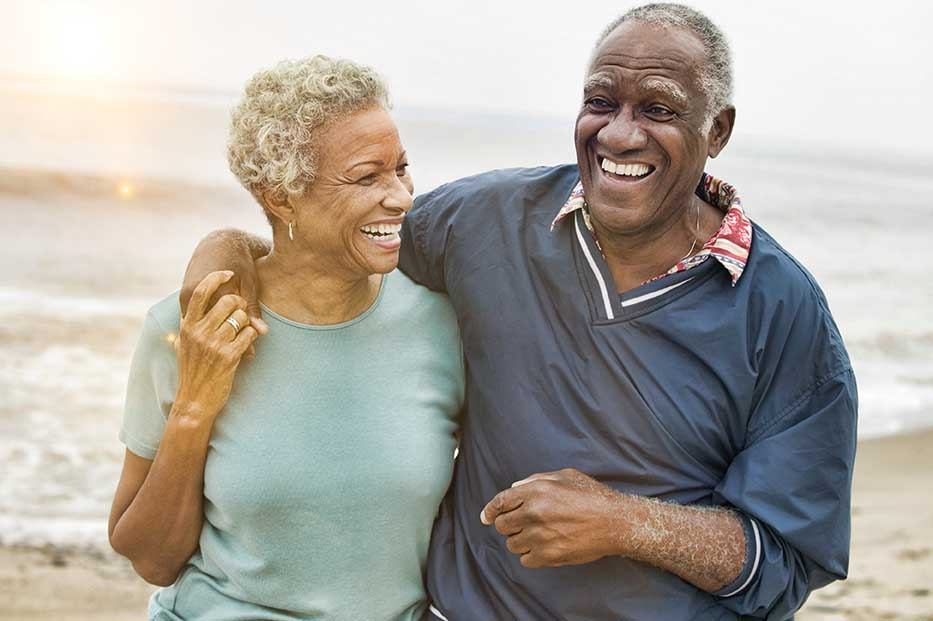 happy senior couple taking walk on beach