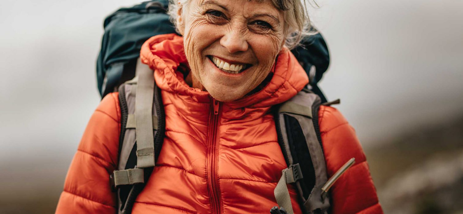 Close up of a senior woman wearing jacket and backpack standing outdoors. Smiling senior woman hiker standing outdoors with fog in the background.