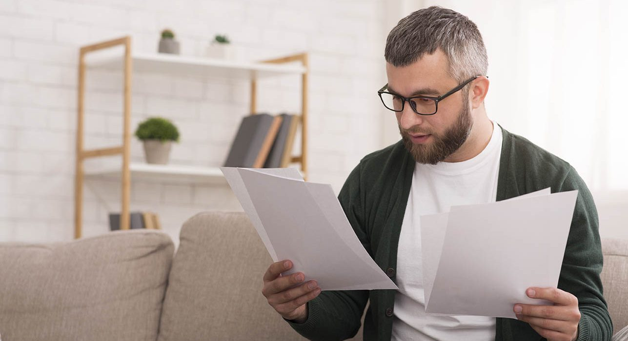 Businessman working at home, reading documents, sitting on the couch, copy space
