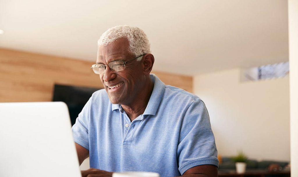 Senior man researching on laptop