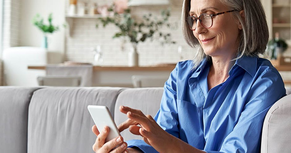 Relaxed mature old 60s woman, older middle aged female customer holding smartphone using mobile app, texting message, search ecommerce offers on cell phone technology device sitting on couch at home.
