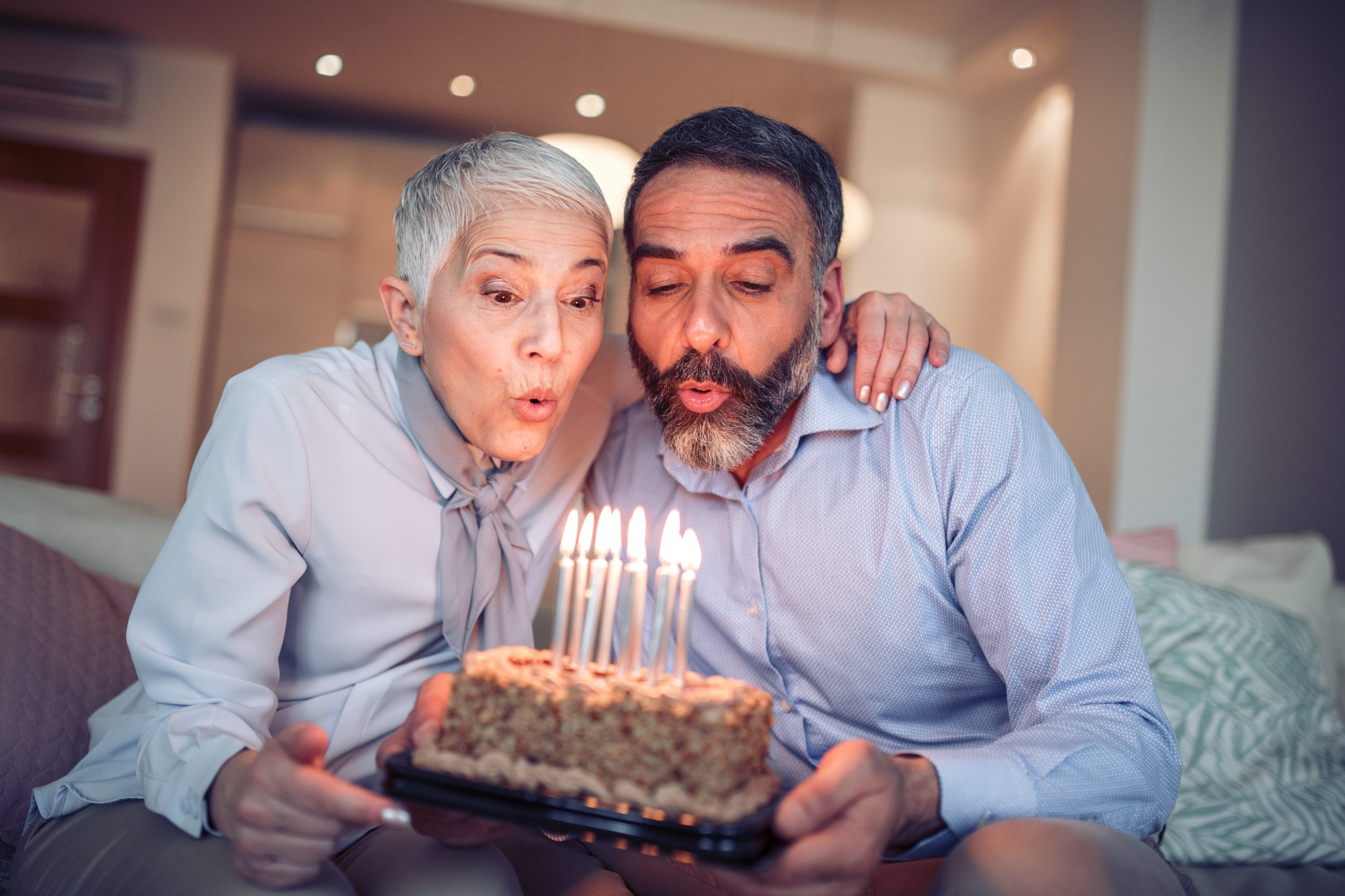 Senior couple blows out candles on birthday cake