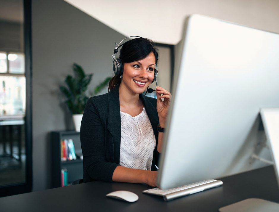 Female consulting manager with headset working in the office.