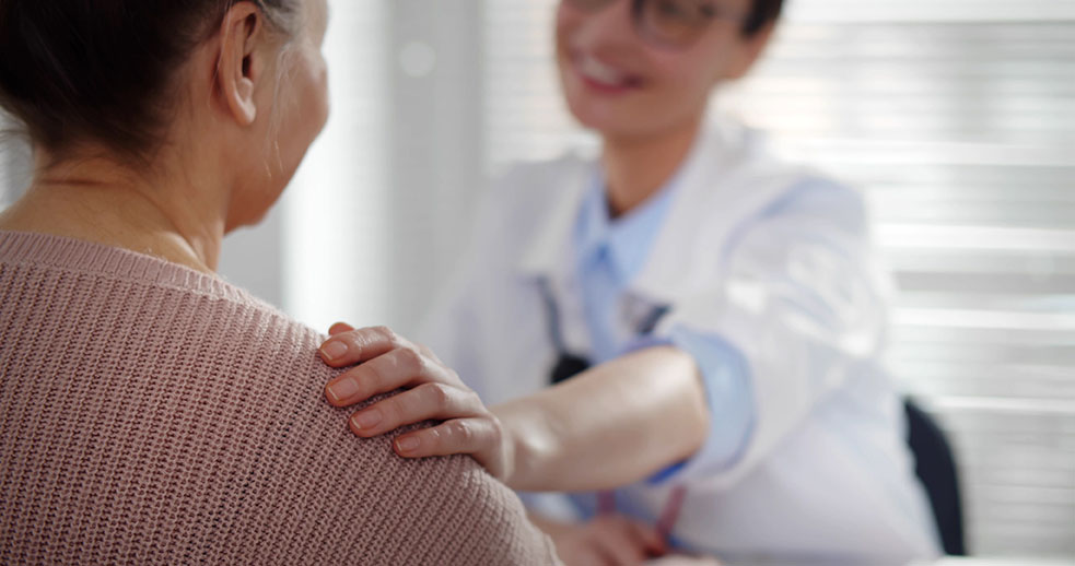 Female doctor holding aged patient by shoulder soothing her fear. Close up of woman therapist supporting and cheering senior patient in clinic office