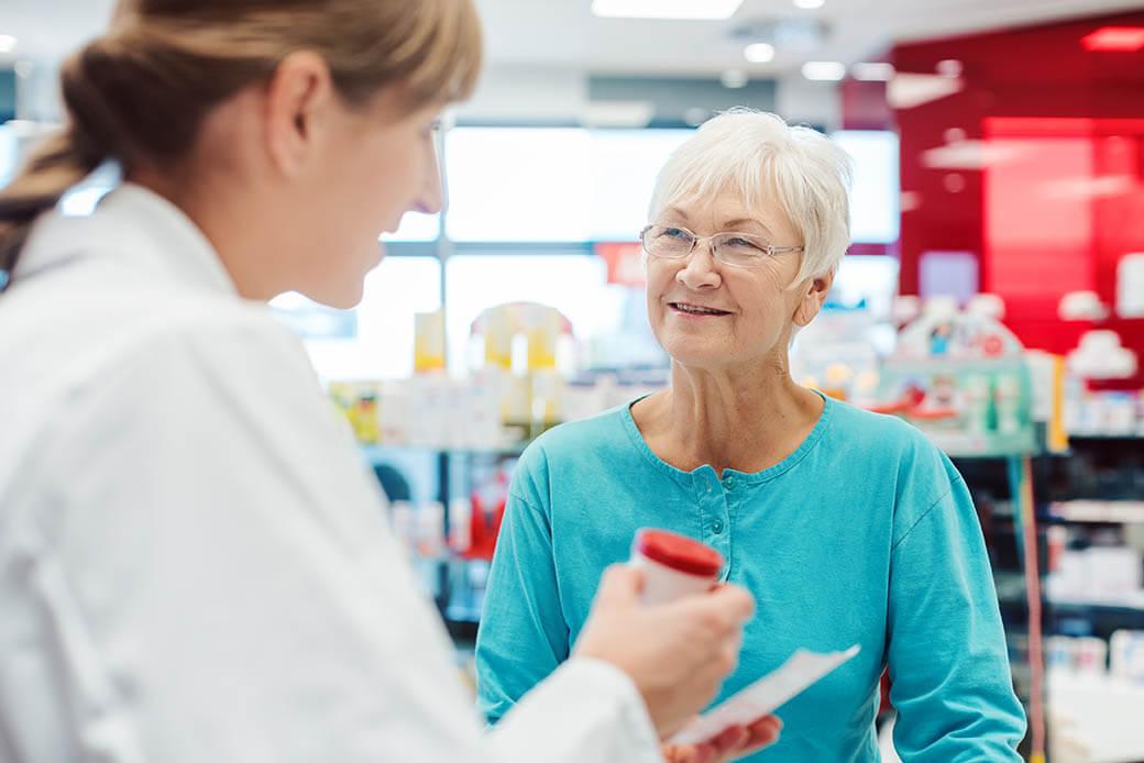 Senior woman in pharmacy talking to the chemist or pharmacist explain effects of a drug