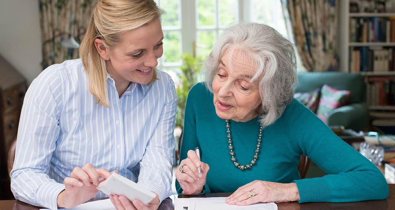 Woman Helping Senior Parent With Medicare Paperwork