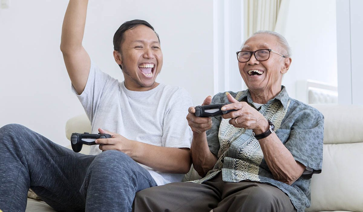 Does my parent qualify for Medicare Part B? text over image ofExcited young man playing video games with his father and sitting on the sofa at home