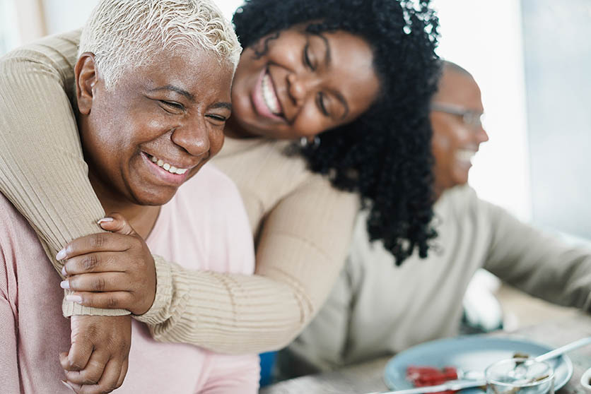 African daughter hugging her mum during lunch meal at home - Love and family concept - Main focus on senior woman face
