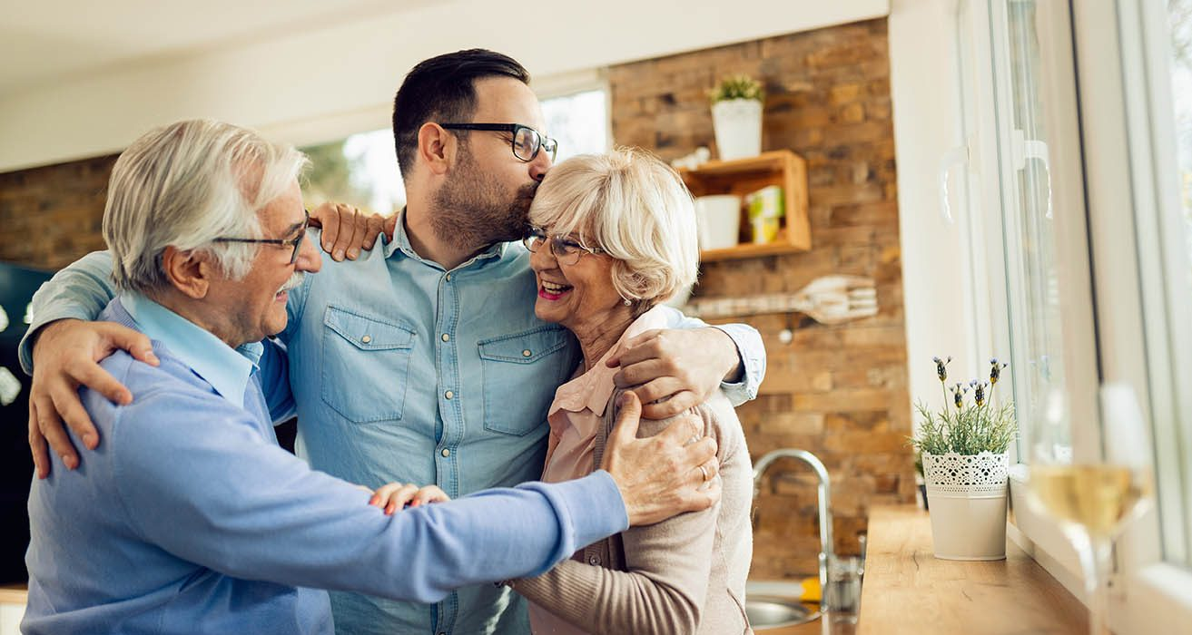 Happy mature couple embracing their adult son while greeting with him in the kitchen.