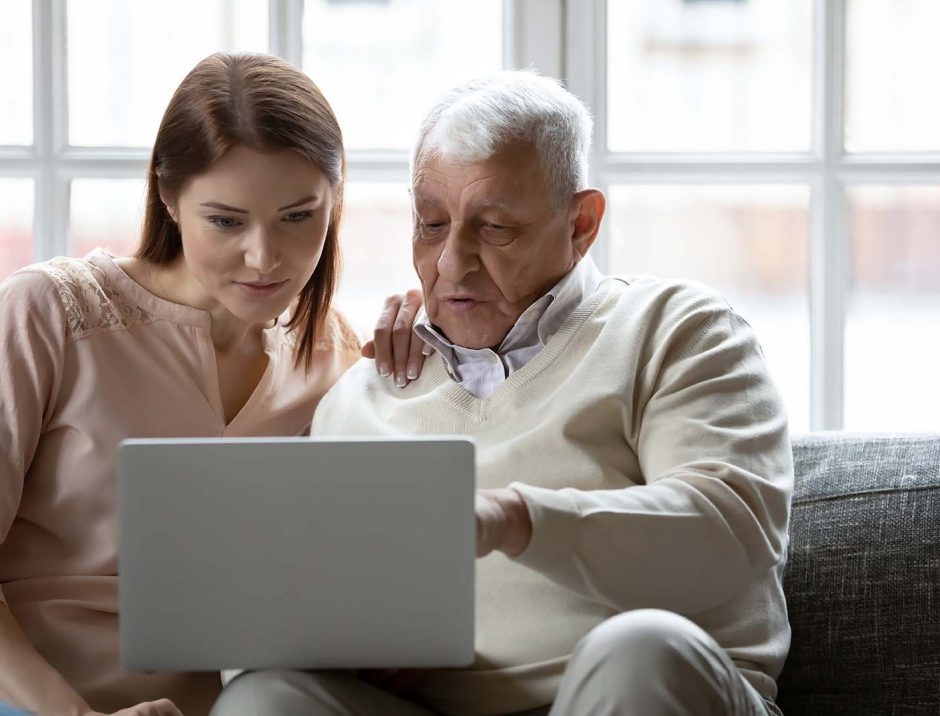 Young woman and older man using laptop together, looking at screen, sitting on couch at home, mature father asking questions to grownup daughter, studying to use computer, pointing at screen